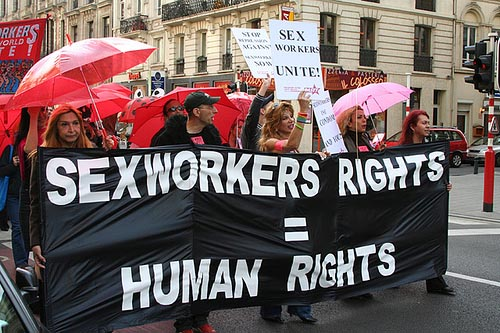 "Picture of protestors marching down a city street carrying a banner that says, ""SEXWORKERS RIGHTS = HUMAN RIGHTS"""